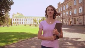 Caucasian woman with computer walks near university. Young blonde student holding laptop walking in campus area. girl with blond hair wearing pink t-shirt and stock footage