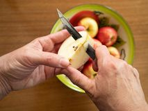 Caucasian Woman Coring an Apple with a Tin Bowl with Apples in t royalty free stock images