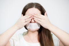 Caucasian woman covering her eyes with hands while mouth sealed with tape Royalty Free Stock Photo