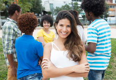 Caucasian woman with crossed arms and large group of internation. Caucasian women with crossed arms and large group of international students Stock Photo