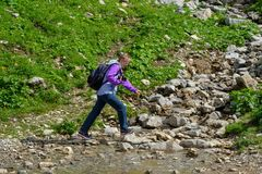 Caucasian woman crossing a mountain creek at a hiking tour Stock Image