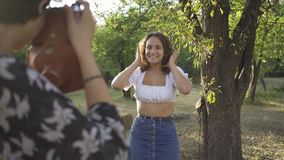 Caucasian woman with curly hair posing in background while her friend taking a photo using old camera in foreground. Attractive caucasian woman with curly hair stock video footage