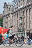 Caucasian woman cycling on the Dam Square, Amsterdam, Netherlands Royalty Free Stock Images