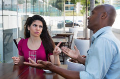 Caucasian woman in discussion with african american man. Caucasian women in discussion with african american men in a restaurant Stock Photos