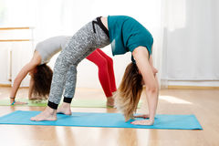 Caucasian woman doing chakrasana posture on mat in yoga classroom Stock Photography