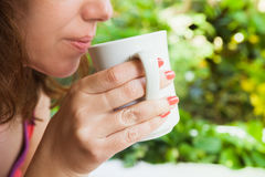 Caucasian woman drinks coffee Stock Images