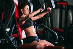 Caucasian woman exercising on shoulder press machine Stock Photos