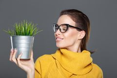 Caucasian woman in eyeglasses holding indoor plant in metal pot. Caucasian young woman in eyeglasses holding indoor plant in metal pot, closed eyes Royalty Free Stock Photos