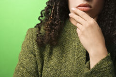 Caucasian woman with hand on chin wearing green clothing. Close-up of young Caucasian woman with hand on chin on green background wearing green clothing Royalty Free Stock Photography