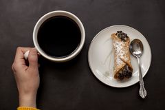 Caucasian woman hand holds coffee cup with italian cannoli on plate on black background Royalty Free Stock Photos