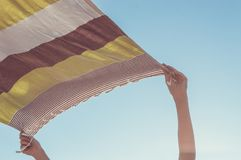 Caucasian woman hands holding a loincloth fabric up in the air to let it dry in the wind. Pastel tons Royalty Free Stock Image