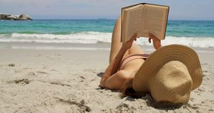 Caucasian woman in hat reading a book on the beach 4k stock video