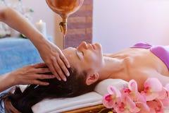 Caucasian woman having Ayurveda shirodhara treatment.  royalty free stock images
