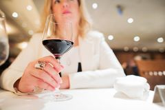 Red Wine Drinker. Caucasian Woman in Her 30s Enjoying Glass of Red Wine in the Restaurant Stock Photo