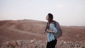 Caucasian woman hiking in desert. Slow motion. Tourist girl wanders on desert canyon edge smiling happy. Israel summer. Caucasian woman hiking in desert. Slow stock video footage