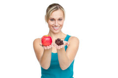 Caucasian woman holding an apple and chocolates. Trying to decide which one to eat Royalty Free Stock Photography