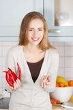 Caucasian woman holding chili peppers and garlic. Stock Photography