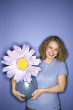 Caucasian woman holding oversized fake flower in vase. Stock Image