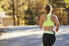 Caucasian woman jogging on country road, back view close up Stock Image