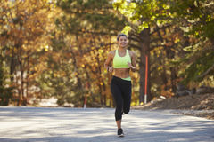 Caucasian woman jogging on country road, front view Stock Image