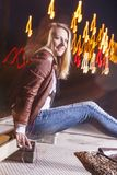Caucasian Woman In Leather Jacket and Blue Jeans. Happy Caucasian Woman In Leather Jacket and Blue Jeans Playing on Rails With Bag Outdoors at Night.Listening To Royalty Free Stock Images