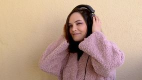 Caucasian  woman listening to music on mobile phone and dancing against yellow pastel  wall. Beautiful caucasian woman listening to music on mobile phone and stock video footage