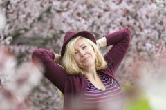 Caucasian woman with long blond hair and purple fedora hat near blossoming tree, arms behind her head with the elbows pointing out Stock Image