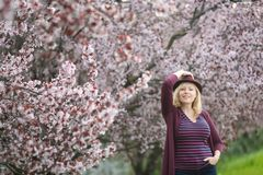 Caucasian woman with long blond hair and purple fedora hat near blossoming tree, one hand up holding hat, second hand in pocket stock photo