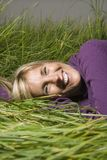 Caucasian woman lying in grass. Stock Image