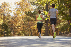 Caucasian woman and man jogging on a country road, back view Stock Image