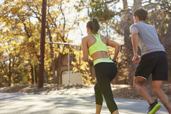 Caucasian woman and man jogging on a country road, back view Royalty Free Stock Photography