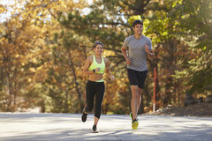 Caucasian woman and man jogging on a country road royalty free stock photos