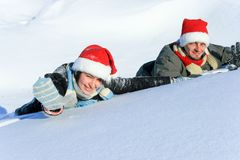 Caucasian woman and man laying on the snow Stock Photos