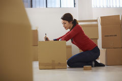 Caucasian woman moving to new apartment with boxes. Mid adult happy woman during move with boxes at new flat and packing carton Royalty Free Stock Photos