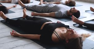 Caucasian woman with multi-ethnic people practicing Savasana