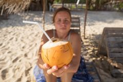 Caucasian woman offering cocnut to her friend. Delicious drink at the tropical beach Royalty Free Stock Images