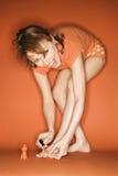 Caucasian woman  painting her toenails. Stock Image