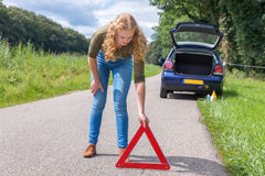 Caucasian woman placing warning triangle on rural road Stock Images