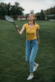 Caucasian woman playing badminton on green field. Attractive caucasian woman playing badminton on green field Stock Photography