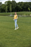 Caucasian woman playing badminton on green field in park. Attractive caucasian woman playing badminton on green field in park Royalty Free Stock Image
