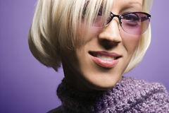 Caucasian woman portrait. Portrait of smiling blond young adult Caucasian woman on purple background wearing sunglasses and scarf Royalty Free Stock Images