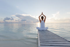 Caucasian woman practicing yoga at seashore Stock Photography