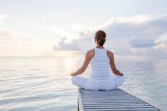 Caucasian woman practicing yoga at seashore Stock Images