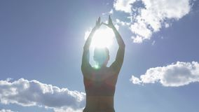 Caucasian woman practicing yoga at seashore with blue sky as background and sun flare in frame. stock footage