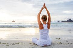 Caucasian woman practicing yoga at seashore of tropic ocean Stock Photo