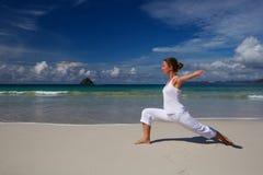 Caucasian woman practicing yoga at seashore of tropic ocean Stock Photos