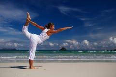 Caucasian woman practicing yoga at seashore of tropic ocean Stock Photo