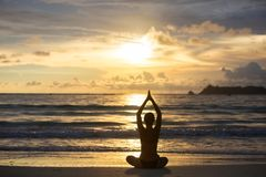 Caucasian woman practicing yoga at seashore of tropic ocean Stock Photos