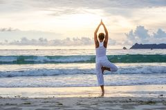 Caucasian woman practicing yoga at seashore of tropic ocean Royalty Free Stock Photo