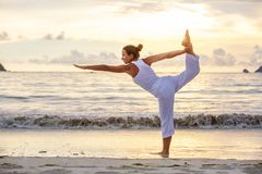 Caucasian woman practicing yoga at seashore of tropic ocean Royalty Free Stock Images